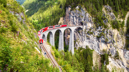 Landwasser Viaduct in Filisur, Switzerland. It is landmark of Swiss Alps. Red train of Bernina Express on high bridge in mountains. Panoramic view of famous railway.