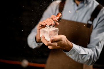 Professional male bartender cutting ice with a special fork in hands in the bar