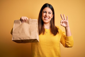Young beautiful woman holding take away paper bag from delivery over yellow background doing ok sign with fingers, excellent symbol
