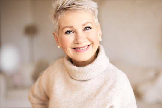 Indoor image of attractive stylish mature Caucasian female wearing cashmere turtle neck sweater looking at camera with joyful broad smile, showing perfect white teeth. Beauty, health and tooth care