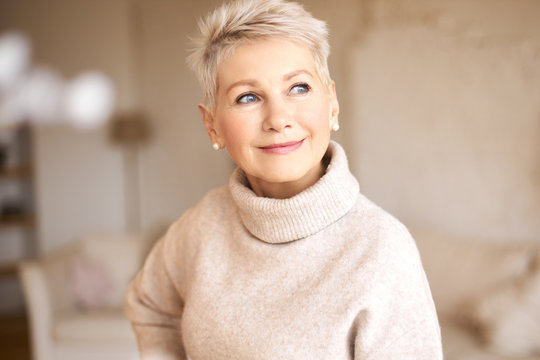 People, age and maturity. Close up shot of elegant blonde middle aged woman with short haircut looking up with pensive smile, thinking about something pleasant, making plans, recollecting old days