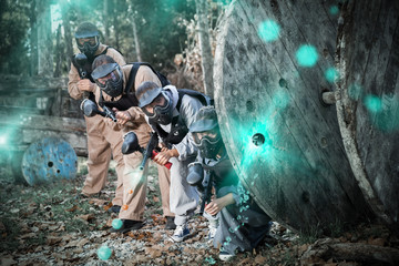 Paintball team aiming outdoors