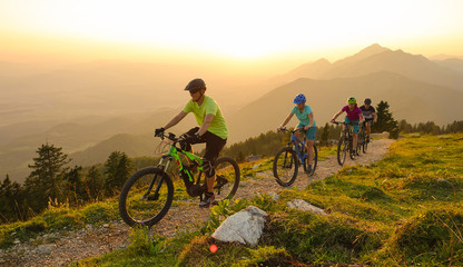 SUN FLARE Cheerful tourists ride electric bicycles up a mountain trail at sunset Fototapete
