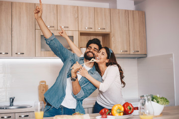 A couple making laughs and singing while preparing a meal. Fotobehang