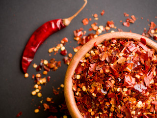 Canvas Prints Hot chili peppers Wooden bowl of crushed red pepper, Cayenne pepper, dried chilli on a motley background. It is a popular spicy condiment for Mexican dishes. Top view.