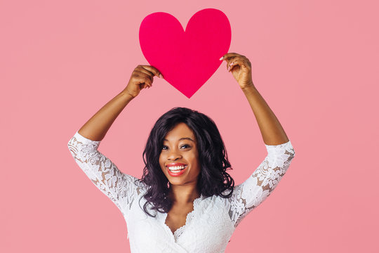 Portrait of  young sexy woman with black curly hair laughing and smiling while holding pink heart above her head, valentineÕs day love, romance and dating concept