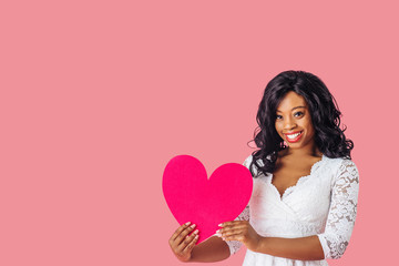 Portrait of young happy woman holding pink heart with big happy smile, valentineÕs day love