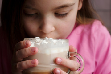 A child drinks hot chocolate with marshmallows.