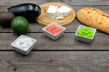 ldelicious dips in bright colors from avocado, eggplant and sheep's cheese with copy space.