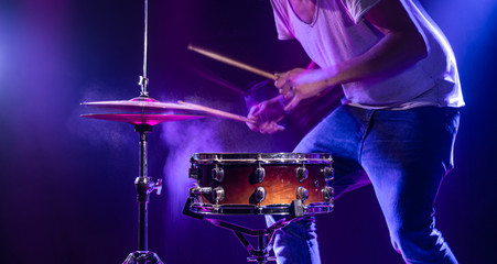 A drummer plays drums on a blue background. Beautiful special effects of light and smoke. The process of playing a musical instrument. Wall mural