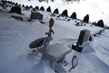 A cutout of a child is placed next to tomb at a cemetery at Des Moines, Iowa,