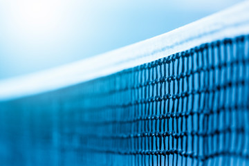 Tennis net and blue court. Individual sport. Blue filter