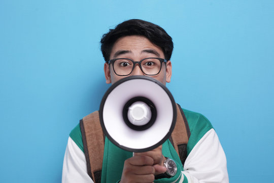 Young Asian male student wearing green baseball jacket shouting on megaphone