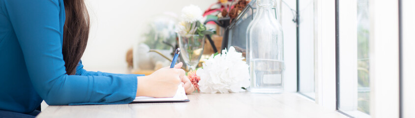 Beautiful portrait young asia woman writer writing on notebook or diary with happy, lifestyle of asian girl is student, female planning working, education and business concept, banner website.
