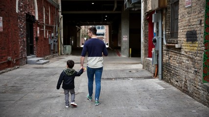 Father and son happily walk through alley of city street