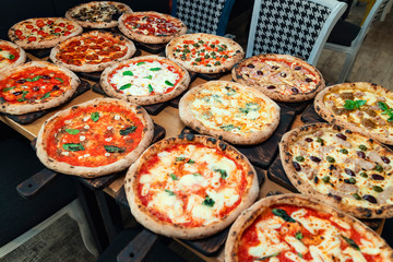 Lots of pizzas on wooden background. Pizza party