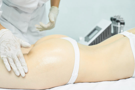 Body massage with oil. Doctor cosmetologist hands. Anti cellulite medical procedure. Legs back treatment