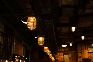 Wall Mural - Loft and rustic style house interiors. Beautiful vintage luxury light bulb hanging decor glowing in dark. Retro filter effect style.