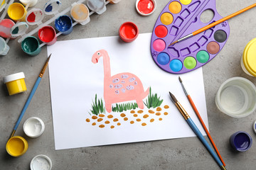 Flat lay composition with child's painting of dinosaur on grey table