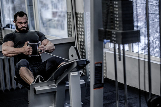 powerful young athlete man with beard pulling heavy weight sitting in sport fitness machine in gym with grimace of effort on his face