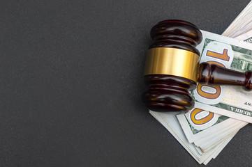 Judge's gavel with money on black.