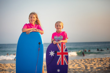Two Aussie girls on the beach with their body boards