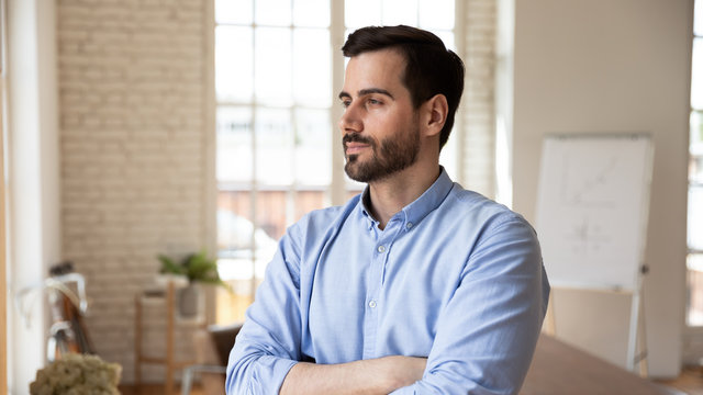Thoughtful confident businessman looking in distance, pondering strategy
