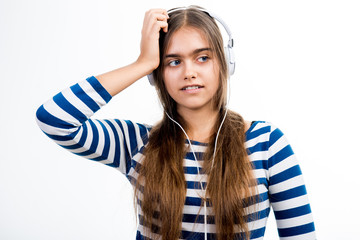 girl in the headphones. Teenager in a striped T-shirt. Girl with long hair in headphones on a white background.  The girl listens to music on the hearphones.