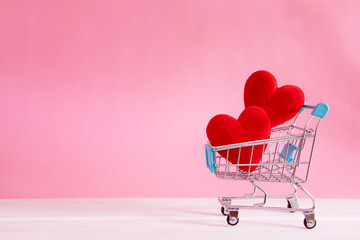 The red Heart shapes  in shopping cart on sweet pink background , the love concept for shopping on valentines day with sweet and romantic moment