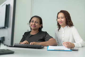 Two businesswomen or corporate professionals working together on an office table with computer