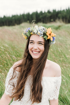 portrait of a natural hippie girl laughing and smiling with flowers in her hair sitting on a green field
