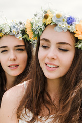 sisters with flowercrowns in fieldclose up portrait of two natural hippie girls with flowers in hair sitting on a green field