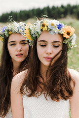 close up portrait of two natural hippie girls with flowers in hair sitting on a green field