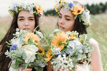portrait of two natural hippie girls with flowers in hair sitting on a green field