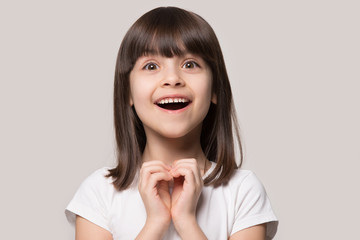 Cheerful excited little girl showing heart love gesture. Fototapete