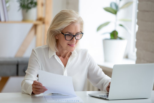 Middle-aged businesswoman typing on pc holds paper prepares report