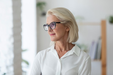 Thoughtful 60s businesswoman looks away planning thinking of new goals
