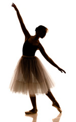 Silhouette of young beautiful ballerina in white tutu and pointe shoes doing dancing pose