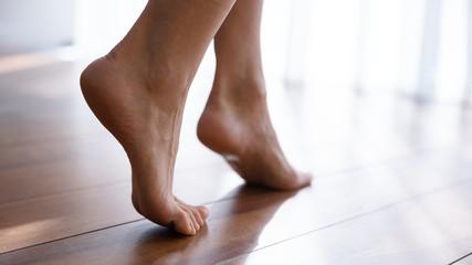 Close up side view beautiful female feet on wooden floor Fotobehang