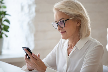 Focused middle-aged businesswoman seated at workplace using smart phone