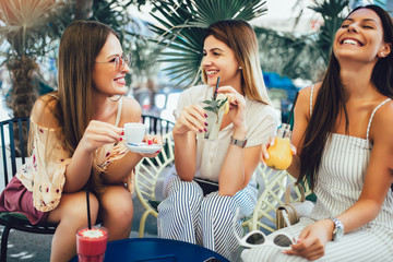 Beautiful girls drinking cocktail in cafe and having fun. Fotomurales
