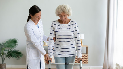 Fototapete - Caregiver teaching older woman to use walker at home