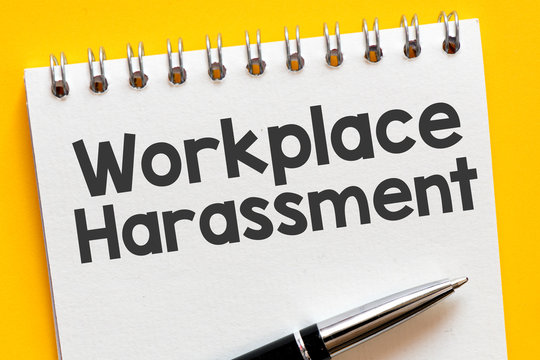 Workplace harassment text on notepad - business concept