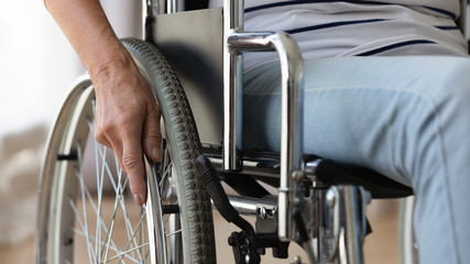 Fotomurales - Close up disabled older woman sitting in wheelchair, touching wheels