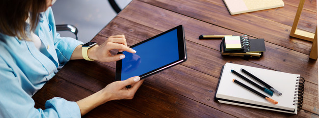 Mockup image of a woman using digital tablet with blank screen on wooden table. Close up photo of female hands holding device vertically