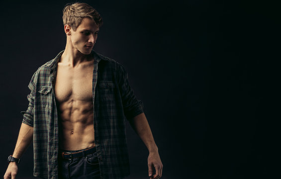 young caucasian man with muscular strong body opened torso, checkered casual shirt on him, he looks side isolated over black background