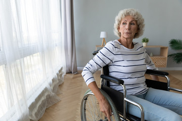 Fotomurales - Thoughtful older woman sitting in wheelchair, holding hands on wheels