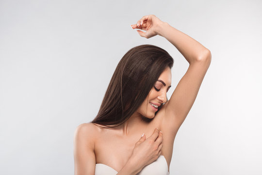 Armpit epilation, lacer hair removal. Young woman holding her arms up and showing clean underarms, depilation smooth clear skin .Beauty portrait.
