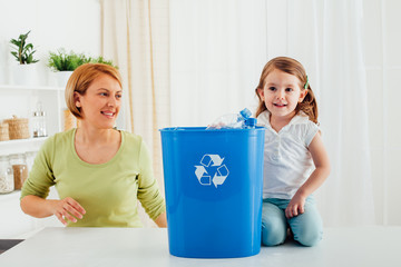 Mother and daughter recycling together