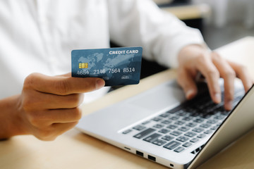 Young man use credit card for shopping payment online on laptop computer application or website....